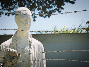 Why Does Power Corrupt? - Weekly Blog Post by Dr. Craig Biehl - statue of man behind barbed wire in a concentration camp
