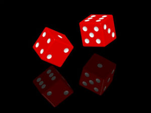Random Chance Behind an Ordered Universe? - Weekly Blog Post by Dr. Craig Biehl - Red dice with reflection on black