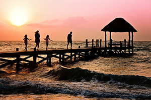 Presuppositions of Faith (4 of 6): Are Miracles Reasonable? - 2 parents and 2 children walking on a pier at sunset